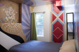 Zoe Jakes room view from the entrance, showing Ganesha alcove and window. Wall elements swirl onto the ceiling.